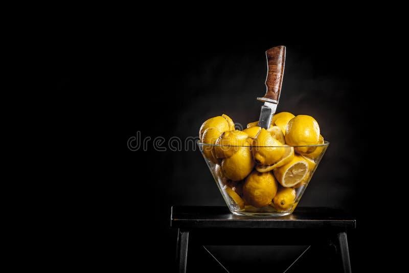透明玻璃花瓶用黄色柠檬和陷进的刀子 免版税库存图片