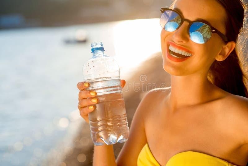 从透明瓶的妇女饮用水  库存照片