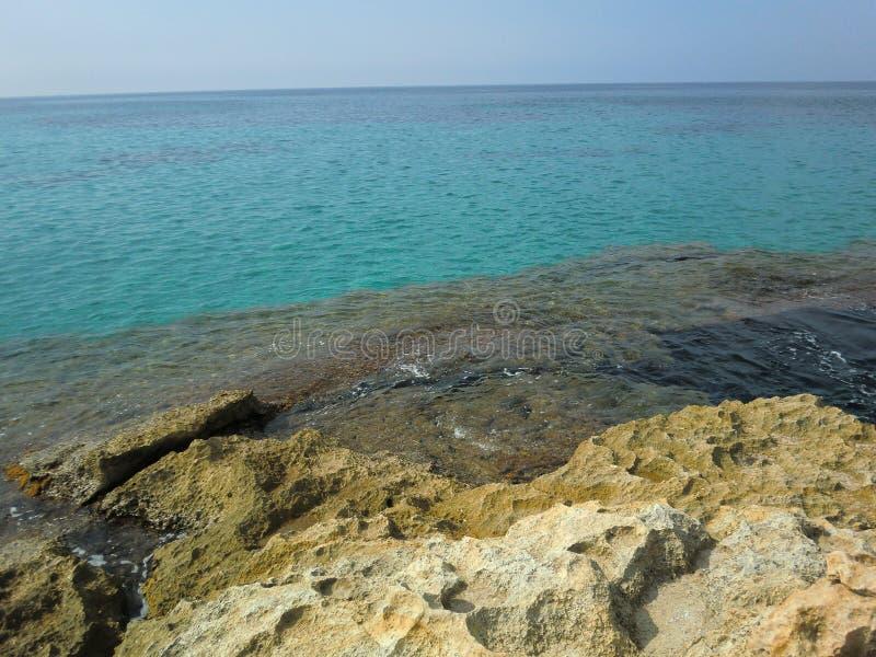 透明的水绿松石海从岩石海岸的 免版税库存照片