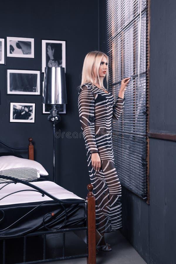 透明礼服的惊人的女孩看与关闭的窗口 图库摄影