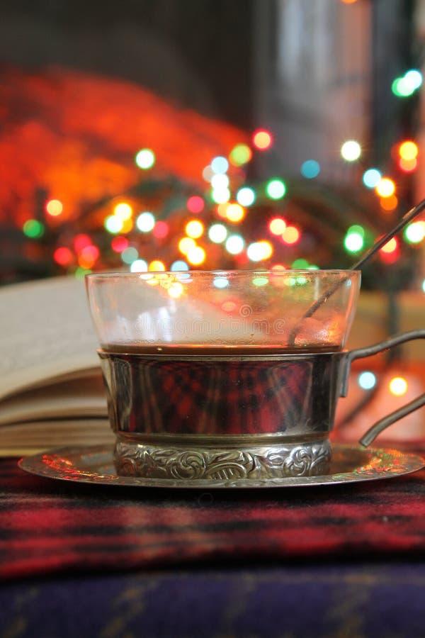透明茶在钢杯座的在一本灼烧的壁炉和圣诞节诗歌选的背景 免版税库存照片