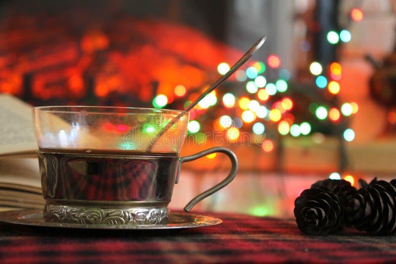 透明茶在钢杯座的在一本灼烧的壁炉和圣诞节诗歌选的背景 免版税图库摄影