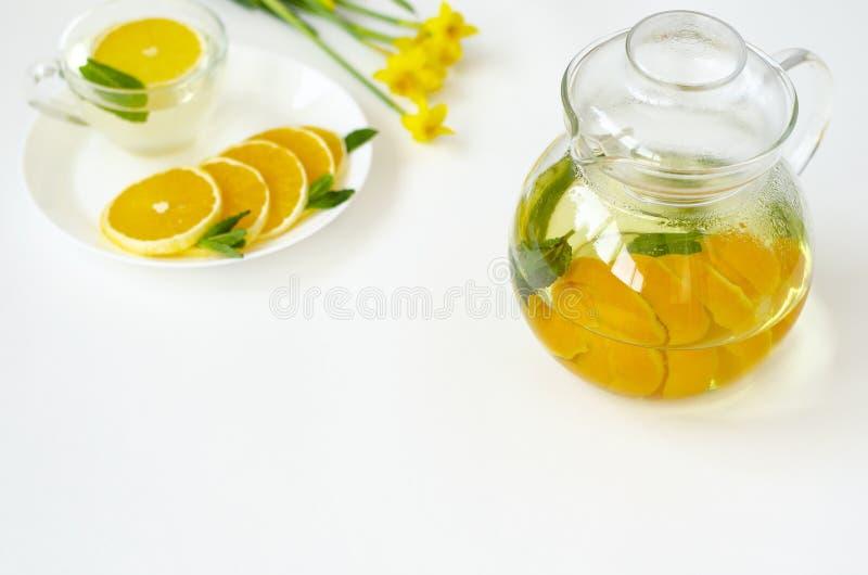 透明茶壶中白色背景橙子薄荷黄水仙花的脱毒茶 Spa和休闲 免版税库存图片