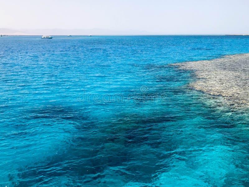透明蓝色periling的海盐水,海,有波浪的海洋风景与美丽的珊瑚礁底部,向agains扔石头 免版税库存照片