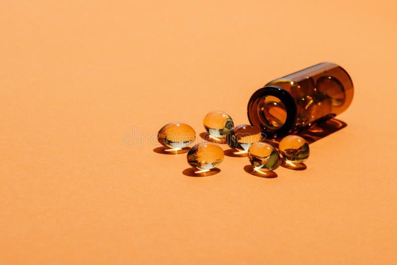 透明黄色药片特写镜头射击从瓶溢出 免版税库存照片