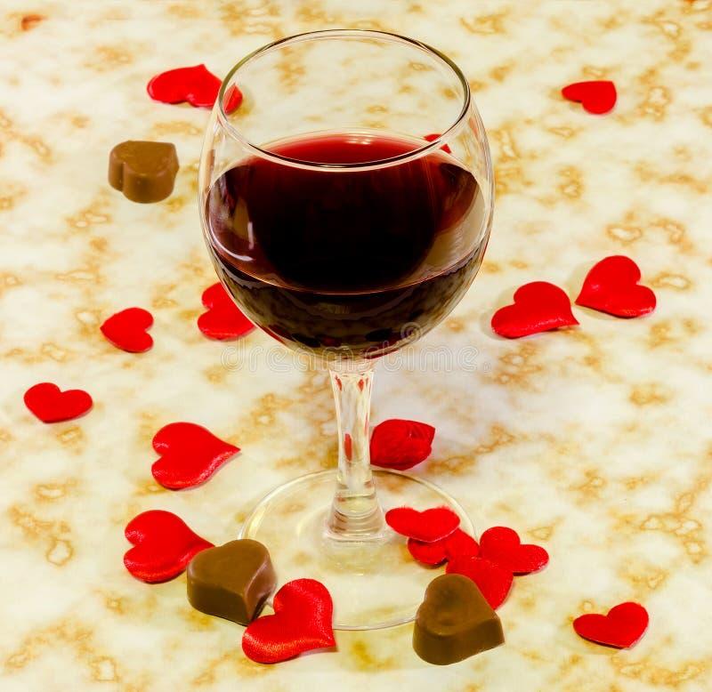 透明玻璃用红葡萄酒、心脏巧克力和纺织品红色华伦泰心脏,老纸背景,关闭 免版税库存照片