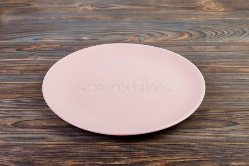 透视图 晚餐的空的桃红色表面无光泽的盘在黑暗的木背景 库存照片