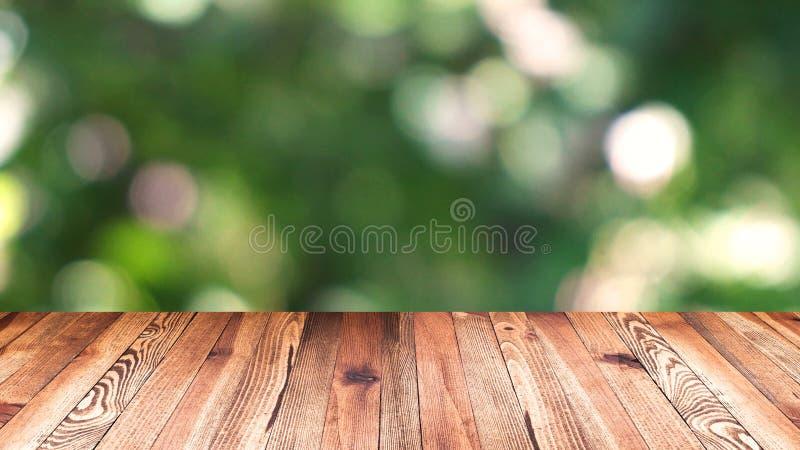 透视木头和bokeh轻的背景 产品显示模板 在迷离移动的自然绿色叶子的木台式 免版税库存图片