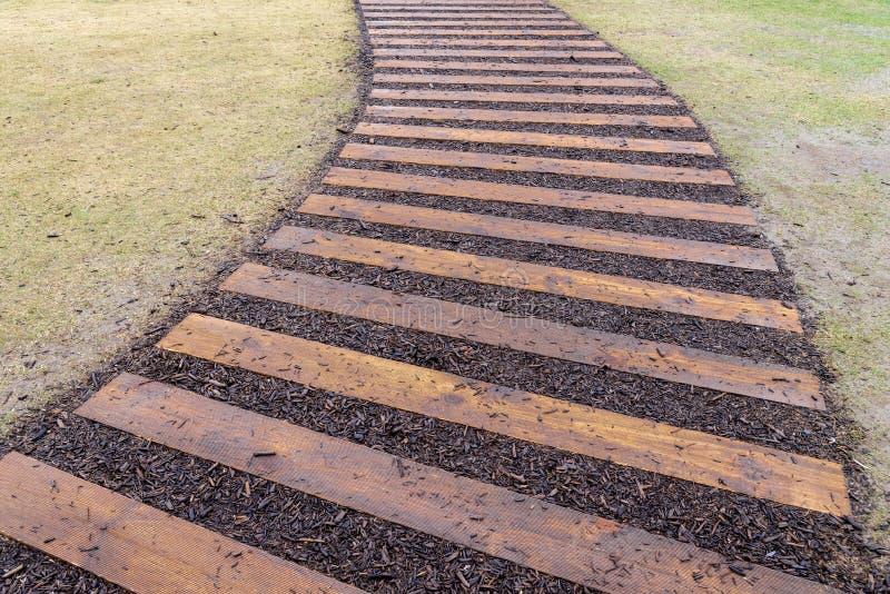 透视的弯曲的木道路走道和绿草草坪竞争 图库摄影
