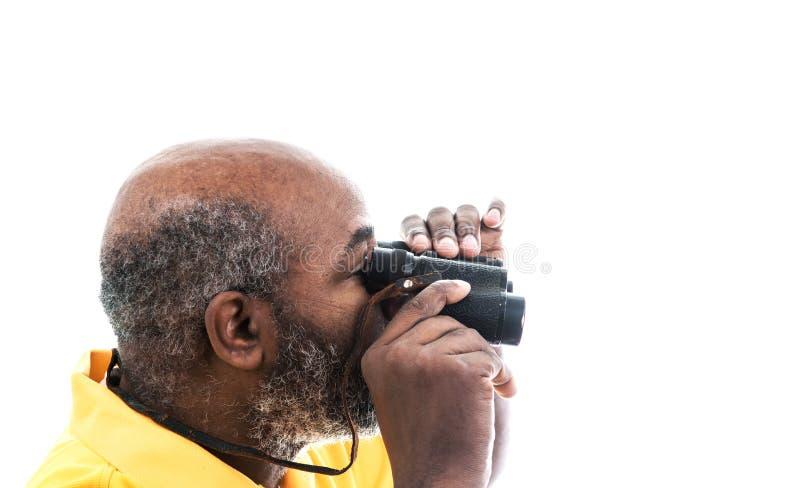 透过白色背景中带复制空间的双筒望远镜寻找的非洲裔美国人 免版税库存照片