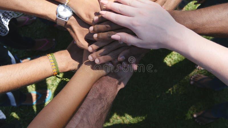逐个一起堆积在团结和配合然后被举的所有种族和颜色的胳膊 许多多种族手 免版税库存图片
