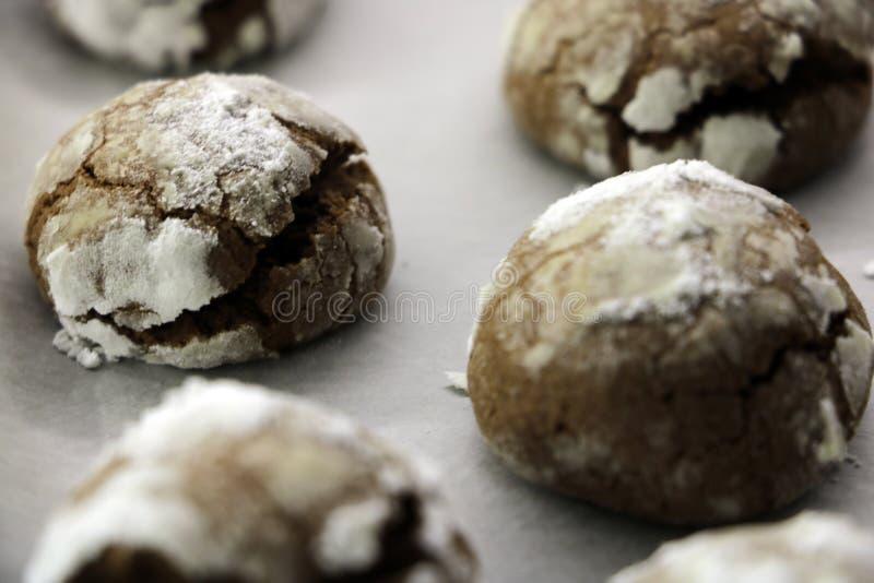 逐步 与糖粉结冰的烘烤的自创巧克力皱纹曲奇饼 在羊皮纸的热的新鲜的曲奇饼 免版税图库摄影