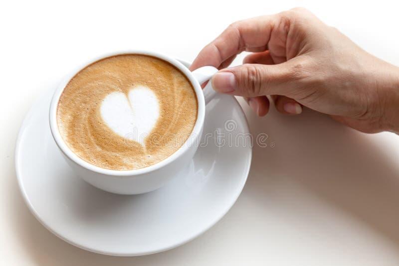 递举行咖啡杯拿铁艺术在白色backgr的心脏形状 库存照片