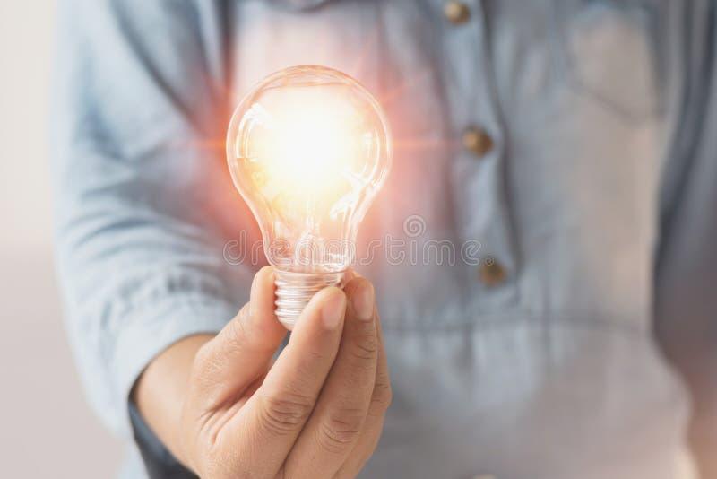 递举行电灯泡、创新和inspiratio的女实业家 免版税库存照片
