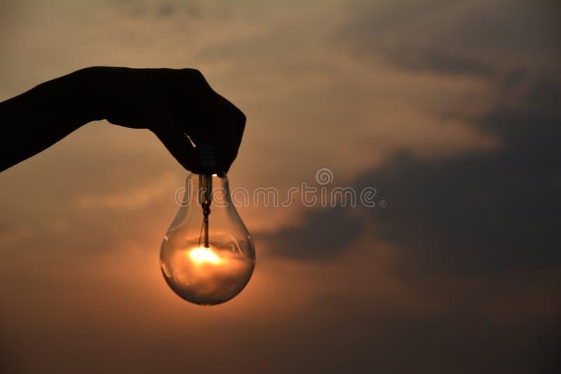 递举行电灯泡想法概念和剪影样式下 免版税库存图片