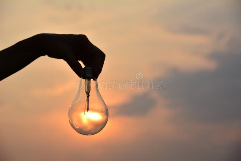 递举行电灯泡想法概念和剪影样式下 库存照片