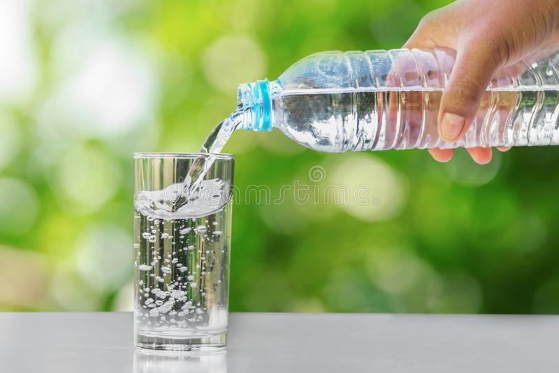 递倾吐的饮用水入在桌上的玻璃形式瓶与 免版税库存图片
