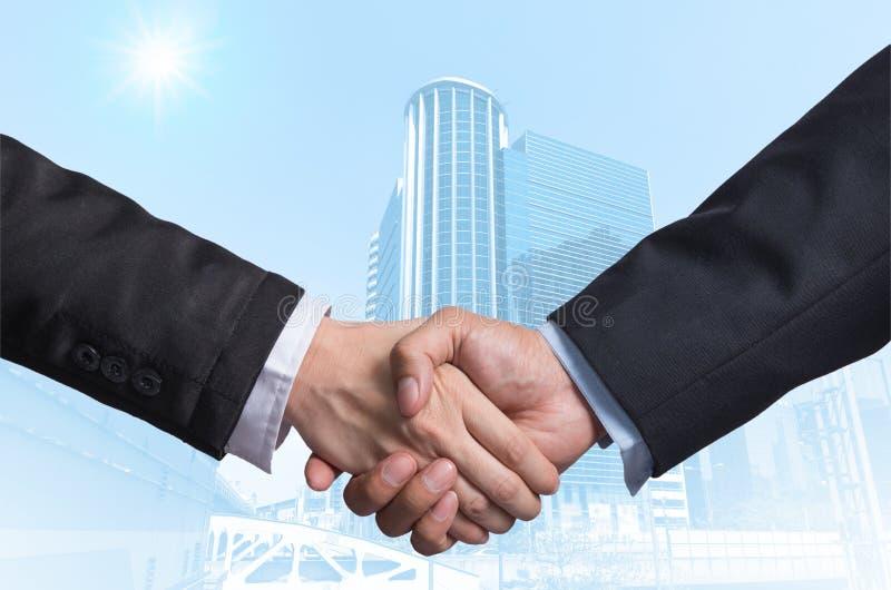 递在一个商人之间的震动在现代企业大厦gla 免版税库存图片