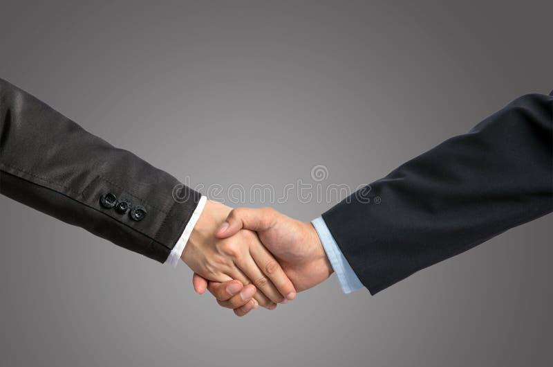 递在一个商人和一名女实业家之间的震动灰色bac的 免版税库存图片