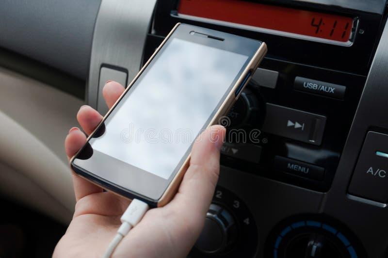 递在汽车,充电器在汽车的插座电话的举行智能手机 免版税库存图片