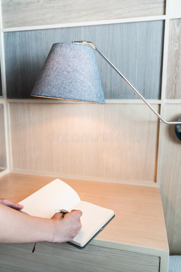 递在笔记本的文字在有灯的书桌 库存照片