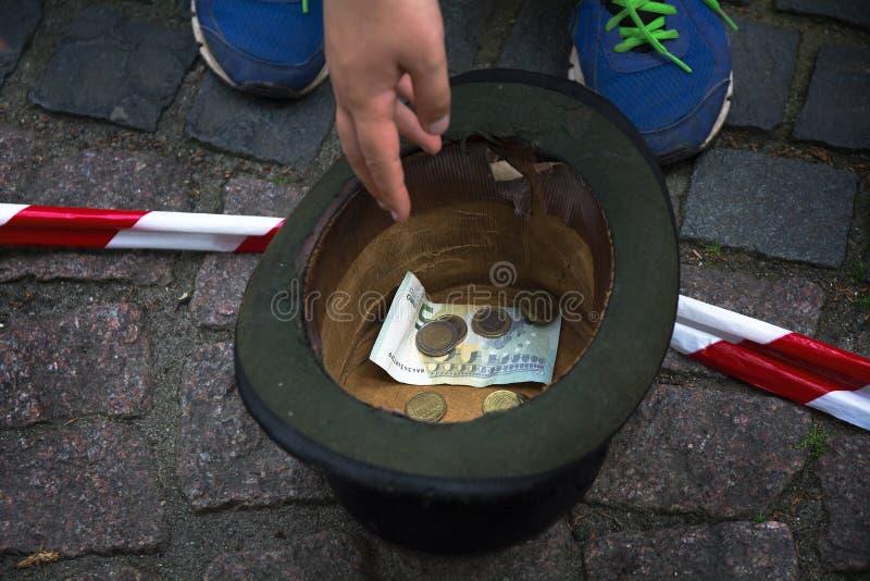 递在陈腐的投掷的金钱从街道艺术家 库存图片