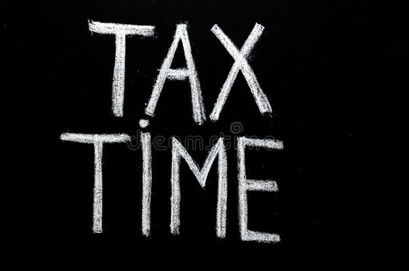 递在黑板的书面词组`税时间` 免版税库存照片