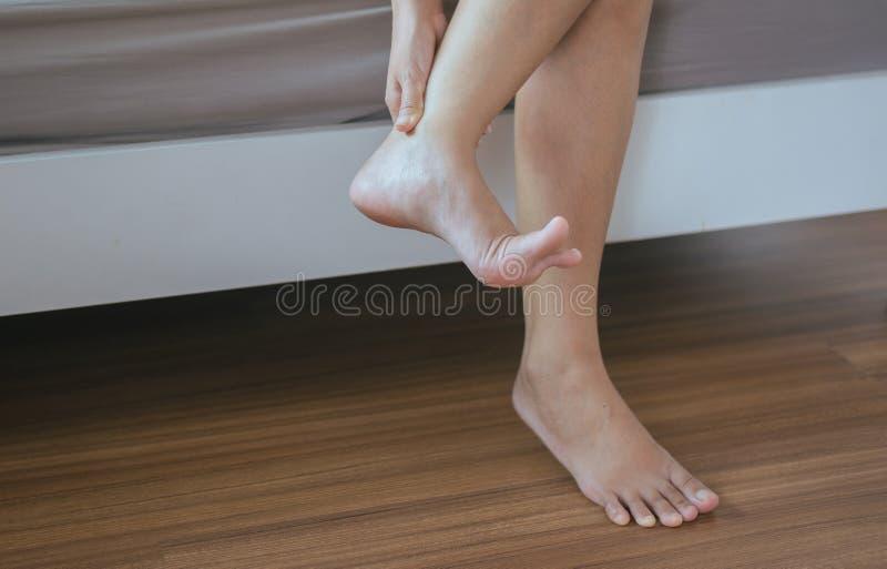 递妇女以脚踝受伤,按摩痛苦,伤害和握痛苦的被扭伤的脚腕的女性 库存图片