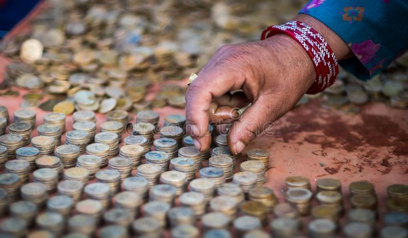 递安排硬币成堆积的专栏,尼泊尔 免版税库存照片