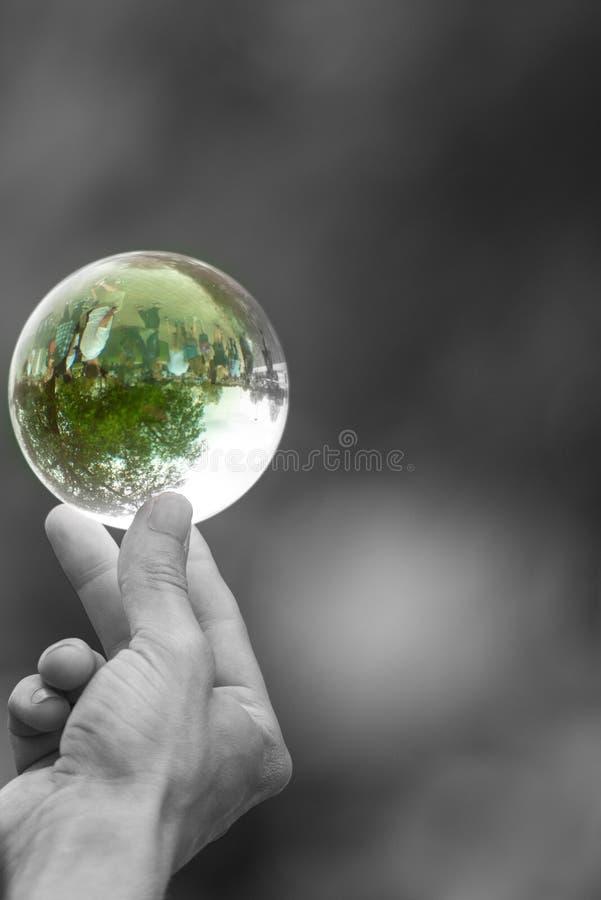 递平衡在象征环境的脆弱的手指的末端的beatuiful玻璃球形 免版税库存图片