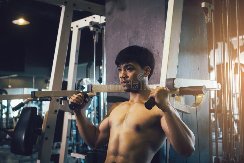 递拉扯酒吧重量的人在室内健身房 免版税库存图片