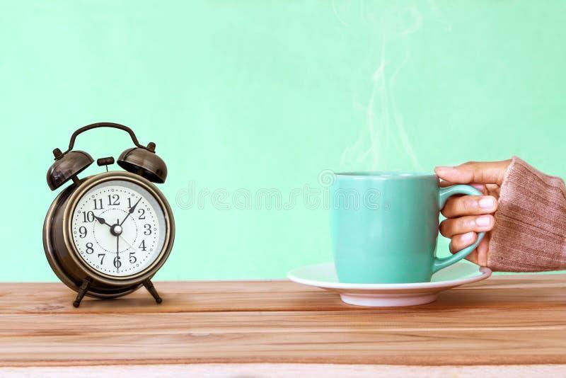 递拿着一个咖啡杯杯子和闹钟在木桌, c上 免版税图库摄影