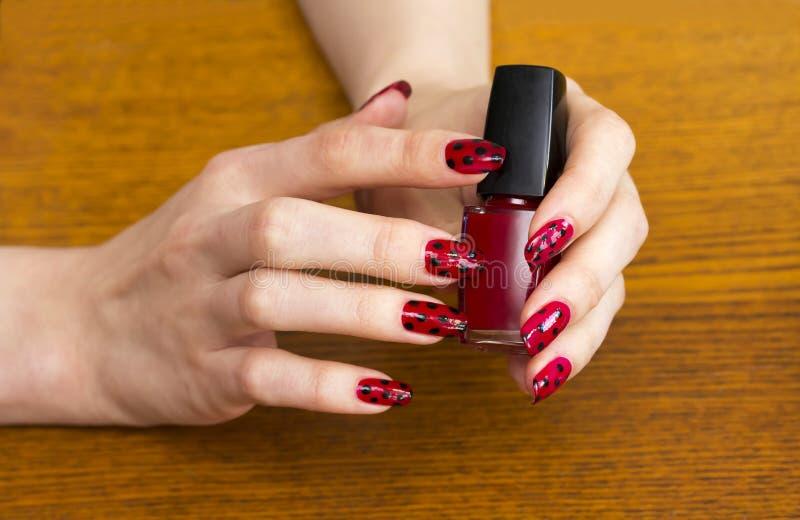 递拿着一个瓶红色指甲油的女孩 免版税库存照片