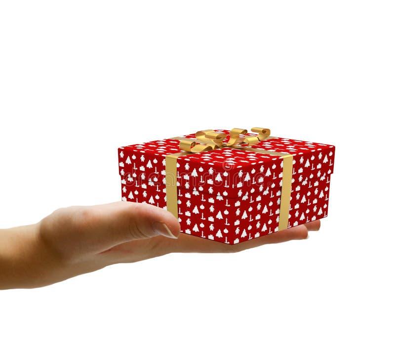 递拿着一件装饰的圣诞节礼物,并且给它在白色背景隔绝了 库存图片