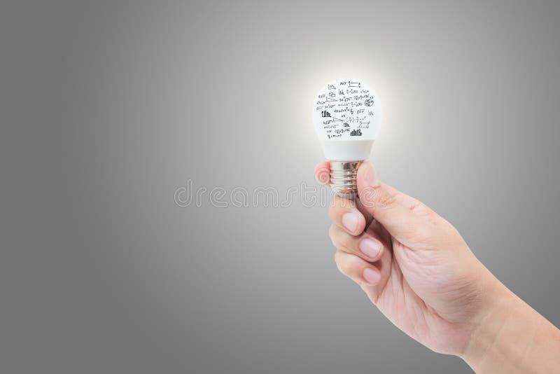 递拿着与明亮发光的电灯泡与算术惯例和图表 图库摄影
