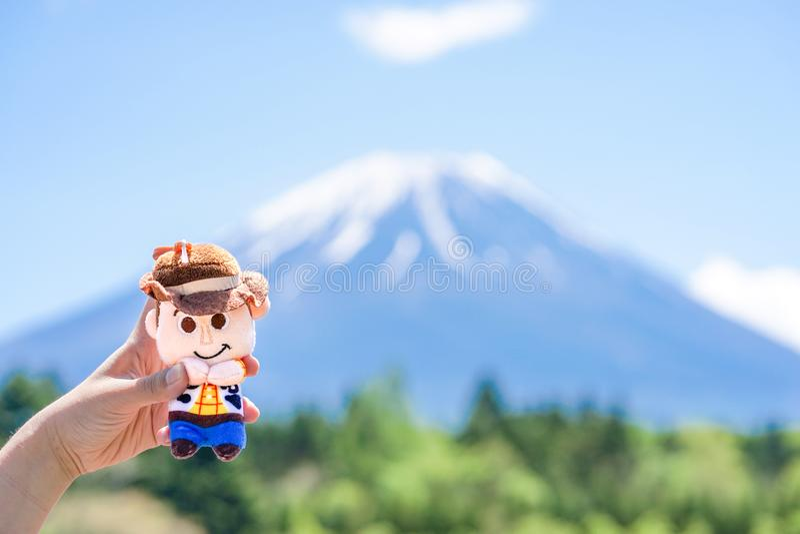 递拿着伍迪,从玩具总动员动画的著名字符一个逗人喜爱的长毛绒玩偶  库存照片