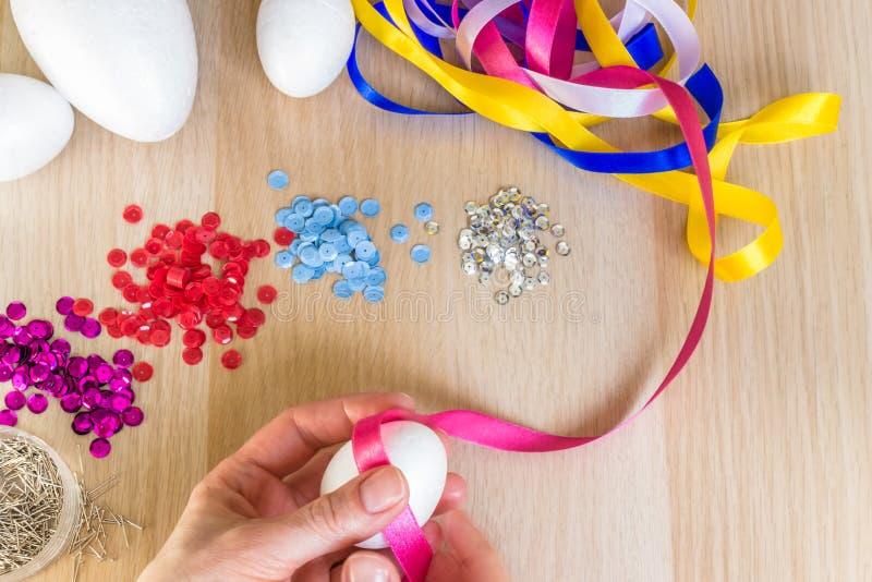 递拿着复活节装饰桃红色丝带的多苯乙烯鸡蛋 库存图片