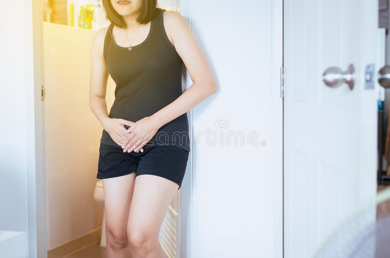递拿着她的裤裆,女性需要的亚裔妇女撒尿洗手间 免版税库存图片