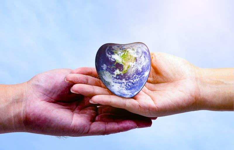 递拿着心脏地球和听心脏的人 库存图片