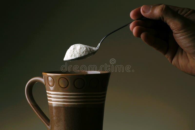 递拿着有咖啡盛奶油小壶的一把匙子对此 库存图片