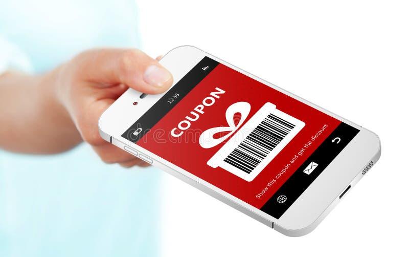 递拿着有圣诞节优惠券的手机在白色 免版税库存照片