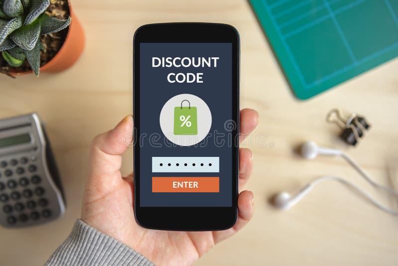 递拿着有折扣代码概念的巧妙的电话在屏幕上 图库摄影