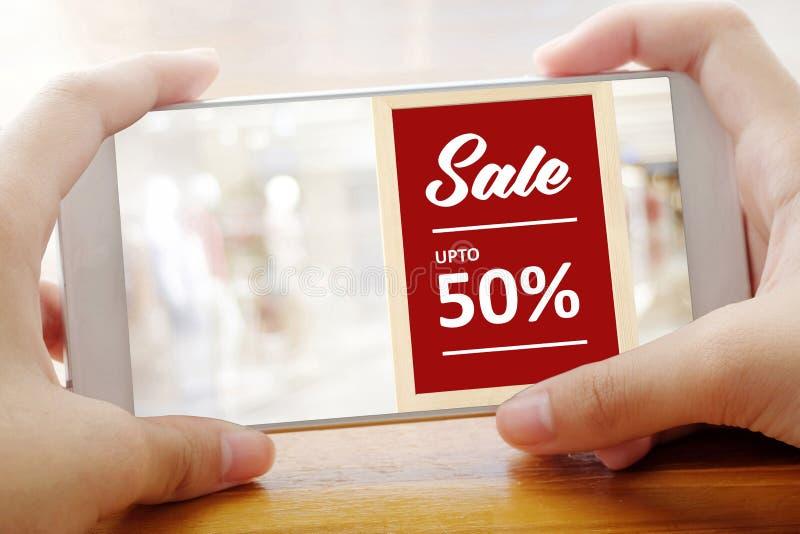 递拿着有推销活动的巧妙的电话在迷离的屏幕上 免版税库存照片