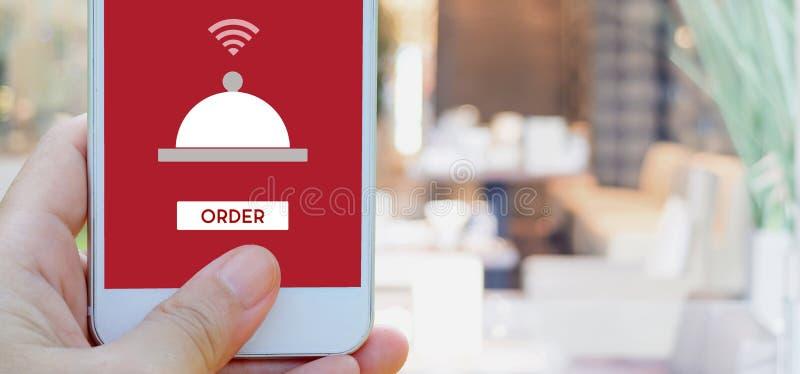 递拿着有食物网上设备的巧妙的电话在屏幕上 免版税图库摄影