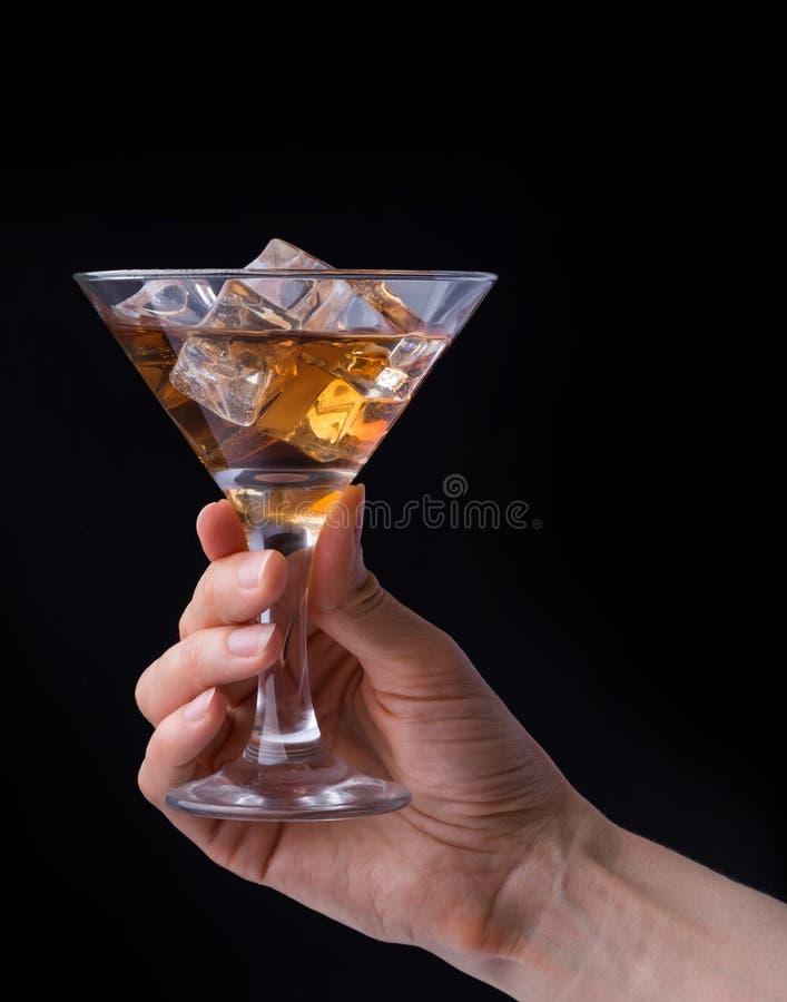 递拿着杯在黑背景的白兰地酒 免版税库存照片