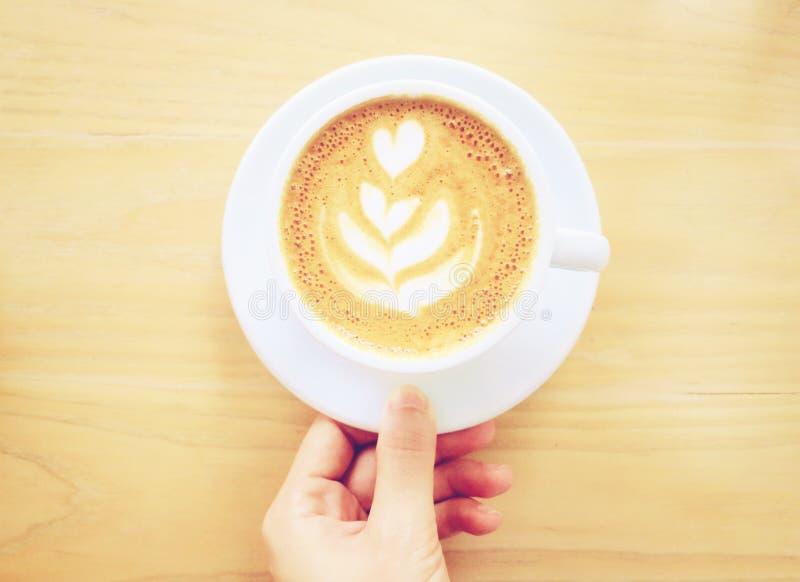 递拿着杯子拿铁或热奶咖啡咖啡 免版税库存照片