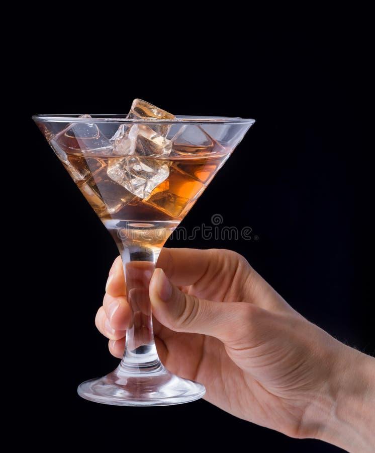 递拿着杯白兰地酒被隔绝在黑背景 免版税图库摄影