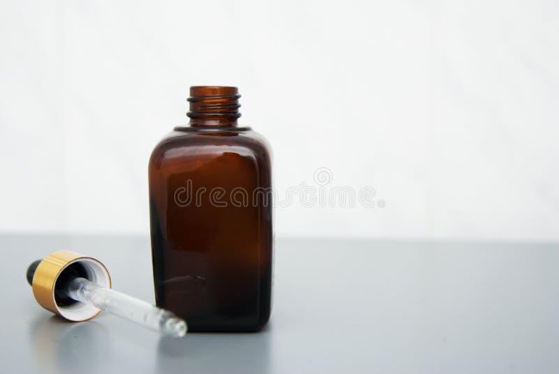 递拿着棕色玻璃瓶被隔绝在灰色桌上 复制空间 秀丽温泉化妆用品,沙龙疗法,简单派概念 免版税库存照片