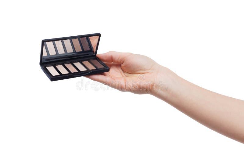 递拿着棕色眼影膏调色板被隔绝在白色 库存图片