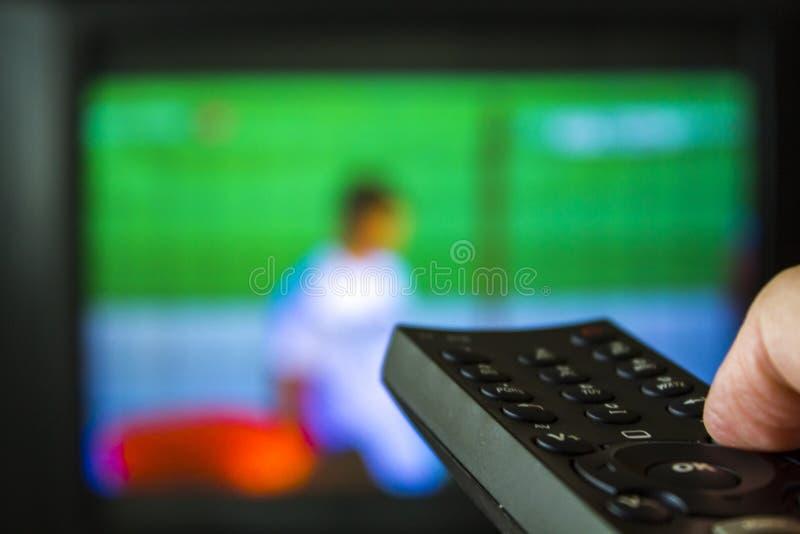 递拿着电视遥控与在背景的电视 图库摄影